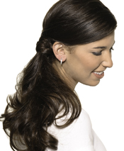"""Sophistication has staying power with a wrapped side pony and side-draped bang. Look """"just-back-from-vacation"""" all year by lightly dusting bronzer on the cheeks, chin and forehead."""