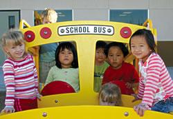 Sydney Young, Chloe Arnott, Emily Cho and Christian Kim enjoy playtime in their little yellow school bus.