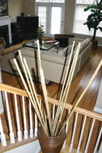 Bamboo stalks can be arranged simply but can make a dramatic statement. These pieces lift the eye up towards an elegantly extended ceiling while posing little distraction to the overall look of this comfortable space.