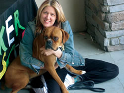 Stephanie Duke, owner of Starpups Depot, cuddles a rescue from the Boxer Rescue before he leaves for his new home. Starpups Depot is celebrating one year in business in June.